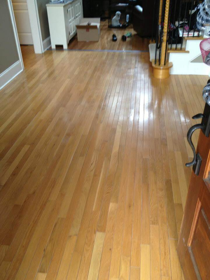 a lightly colored brown hardwood floor with some minor signs of wear and tear.